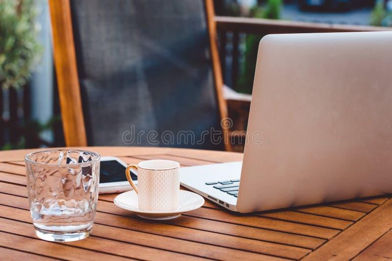 膝上型计算机、一杯咖啡和一杯在一张木桌上的水 免版税图库摄影