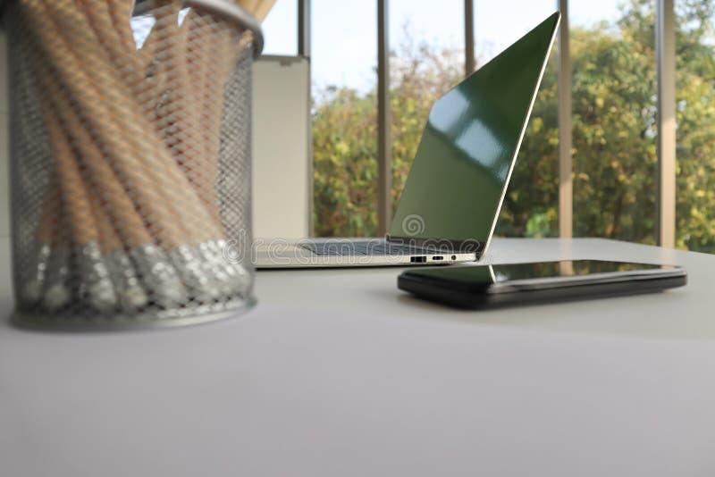 膝上型计算机、手机和铅笔在白色书桌上 免版税库存图片