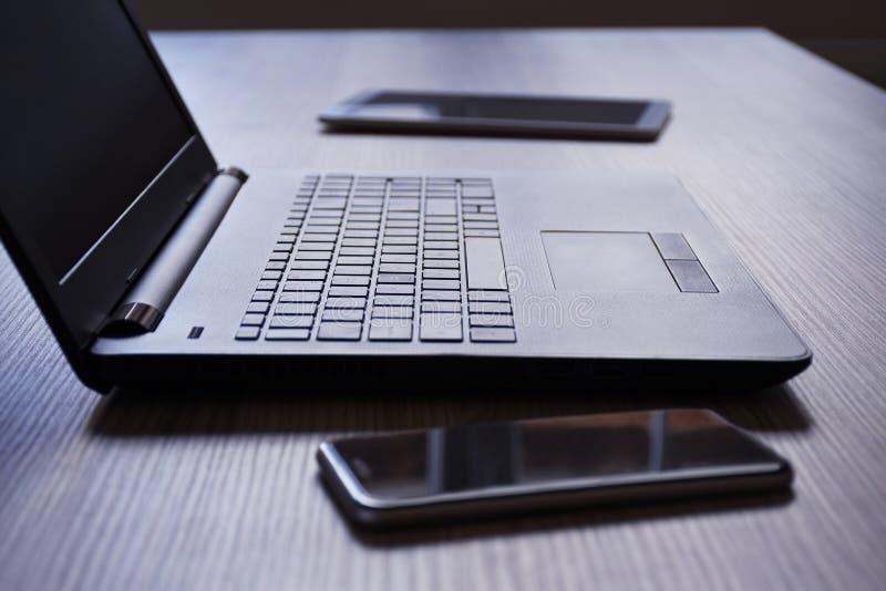 膝上型计算机、数字片剂和智能手机在书桌上 免版税库存照片