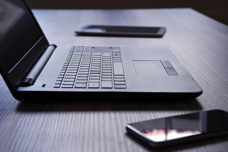 膝上型计算机、数字片剂和智能手机,在书桌上 免版税库存照片