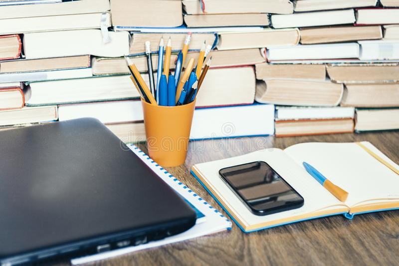 膝上型计算机、智能手机、堆书,笔记本和铅笔在橙色塑料持有人在木桌,教育概念背景上 免版税库存照片