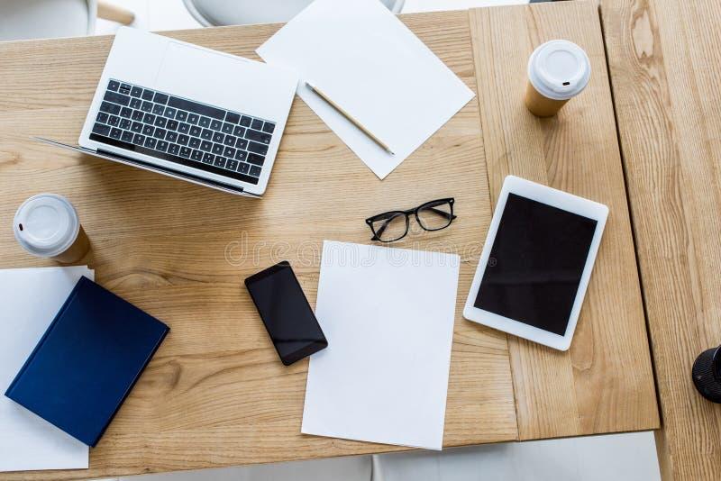 膝上型计算机、智能手机和片剂高的看法在桌上 免版税库存照片