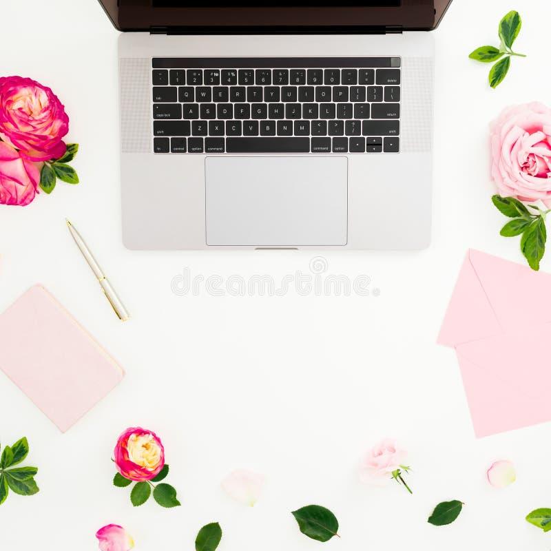 膝上型计算机、玫瑰花、日志、笔和信封在白色背景 平的位置 顶视图 与拷贝空间的女性构成 免版税库存图片