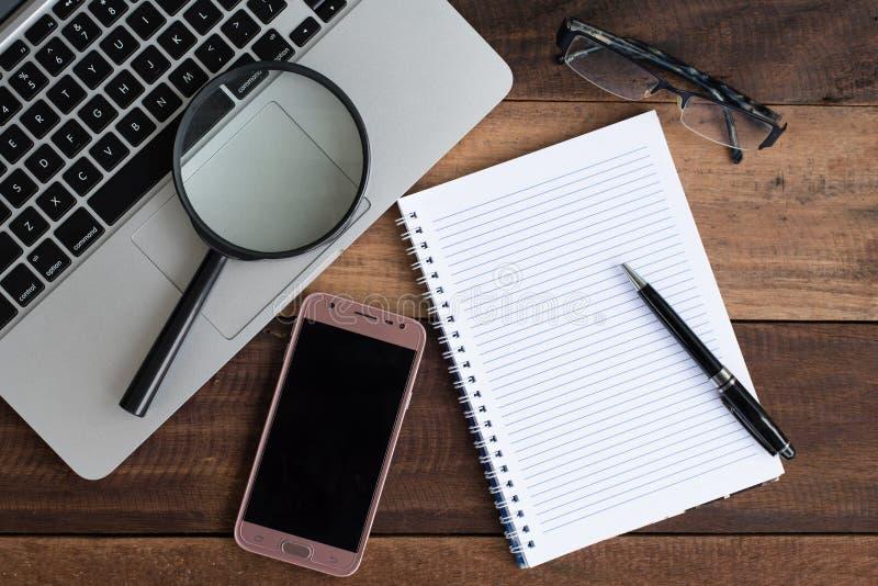 膝上型计算机、笔记本、智能手机、景象和放大镜在木桌上 库存照片