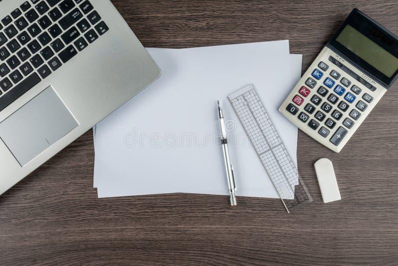 膝上型计算机、纸笔统治者计算器和橡皮擦在工作书桌上 免版税图库摄影