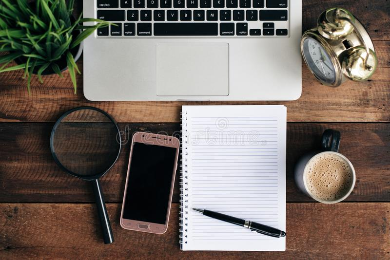膝上型计算机、绿色植物、时钟、放大镜、电话、咖啡和空白的笔记本在一张木桌上 免版税图库摄影