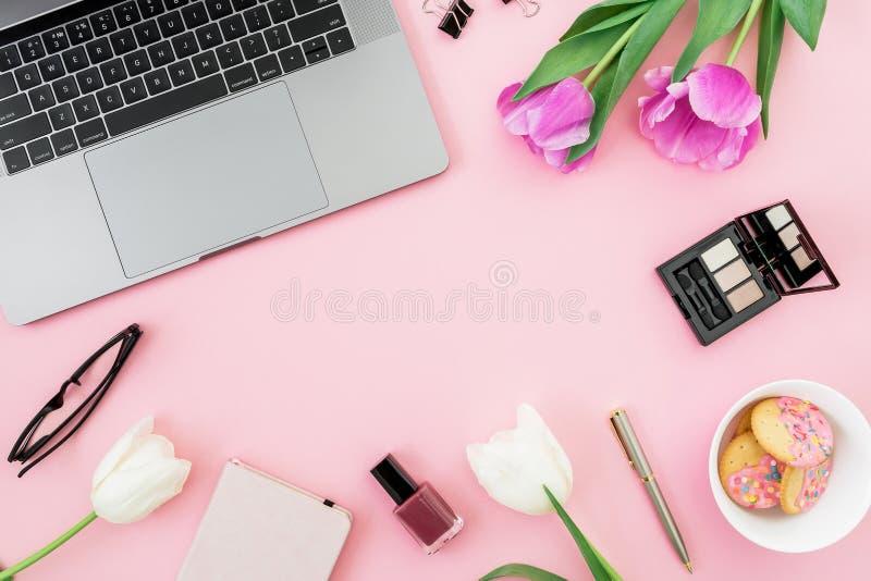 膝上型计算机、郁金香花与玻璃和曲奇饼在桃红色背景 平的位置 顶视图 与拷贝温泉的自由职业者或博客作者概念 免版税图库摄影
