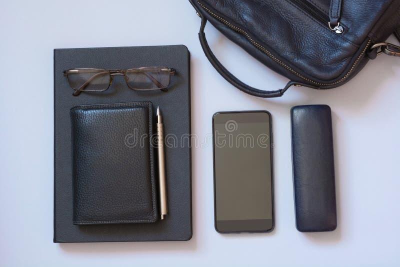 膝上型计算机事务的书包、机动性、笔记本、笔和精神辅助部件在蓝色 平的位置 库存照片