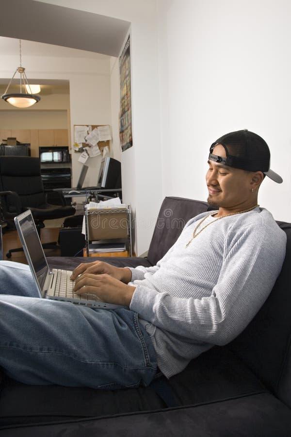 膝上型计算机人坐的沙发使用 免版税库存图片