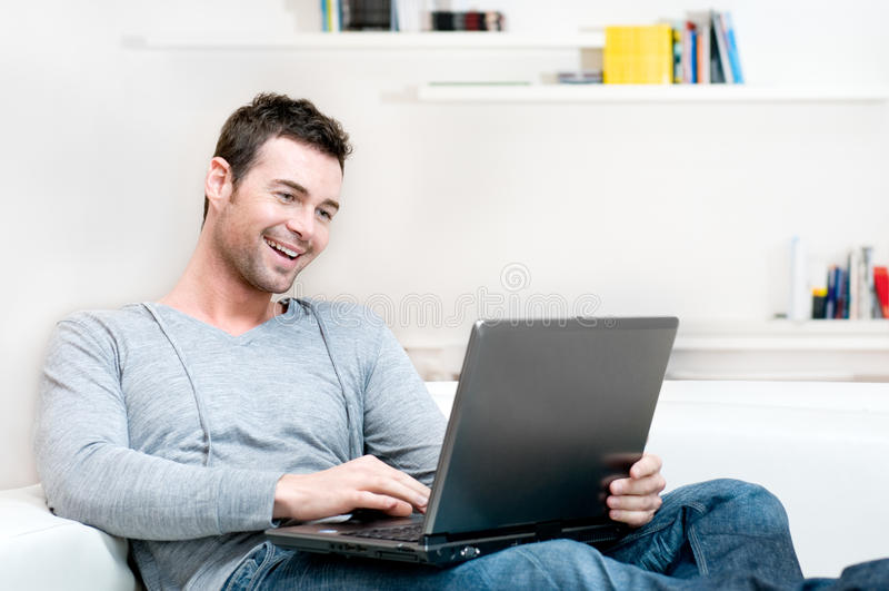 膝上型计算机人微笑的运作的年轻人 图库摄影