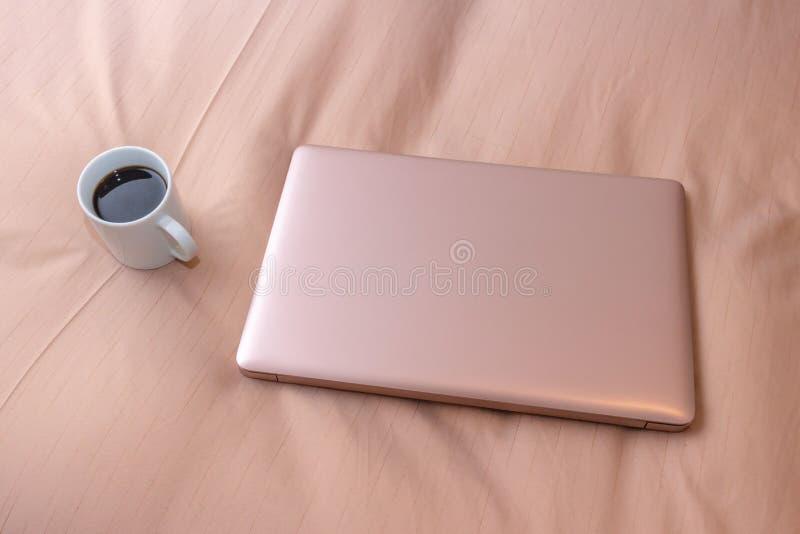 膝上型计算机和一杯咖啡在床上的,出差 免版税图库摄影