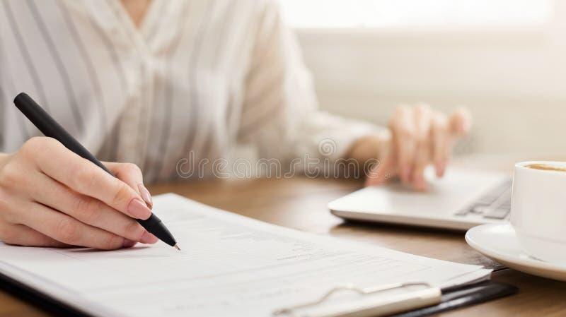 膝上型计算机和文字笔记的年轻女性企业家 库存照片