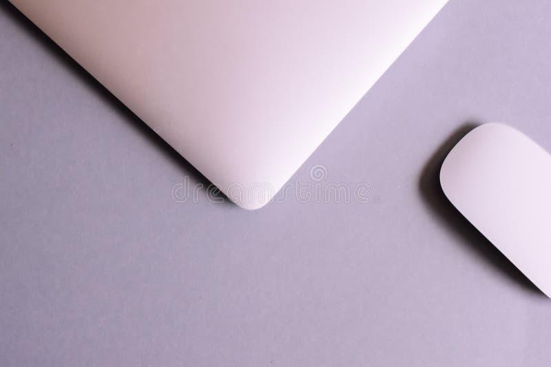 膝上型计算机和无线鼠标在桌上 免版税库存图片