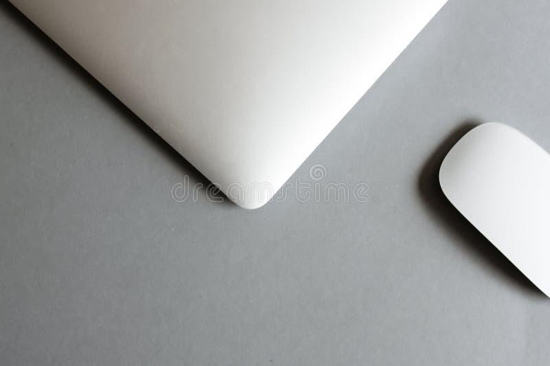 膝上型计算机和无线鼠标在桌上 免版税图库摄影