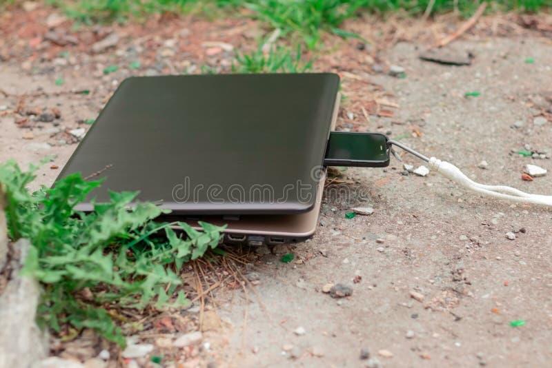 膝上型计算机和智能手机在午餐期间 强有力的设备吸收过时的小配件 ?? 免版税库存图片