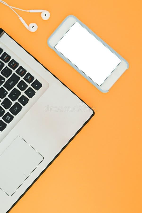膝上型计算机和智能手机有一个白色屏幕和耳机的在橙色背景 免版税库存照片