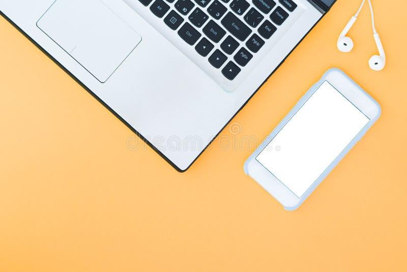 膝上型计算机和智能手机有一个白色屏幕和耳机的在橙色背景 库存照片