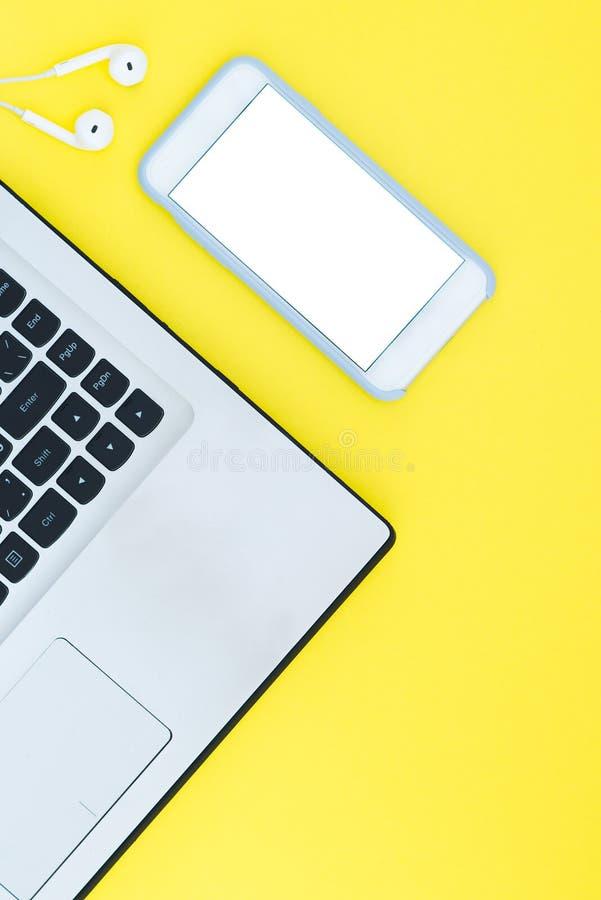 膝上型计算机和智能手机有一个白色屏幕和耳机的在黄色背景 免版税库存图片