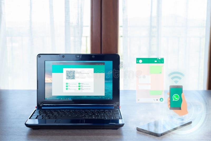 膝上型计算机和智能手机有whatsapp图表的 库存照片
