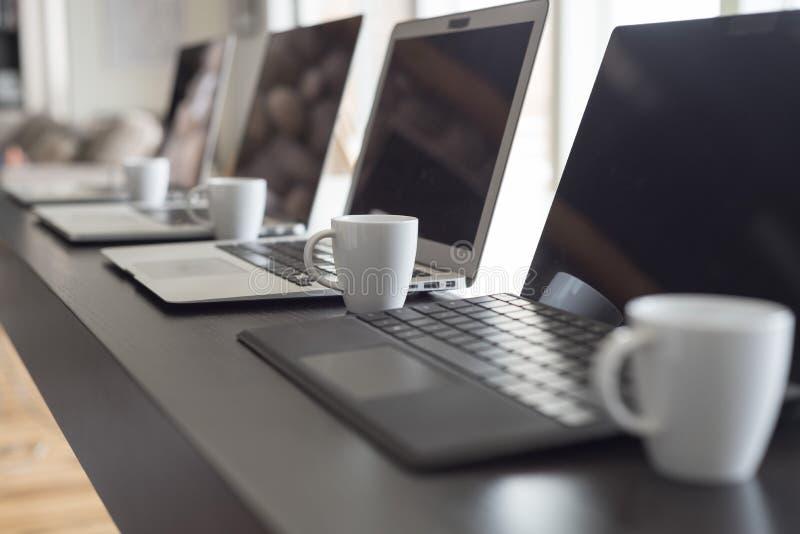 膝上型计算机和浓咖啡排队的侧视图 免版税图库摄影