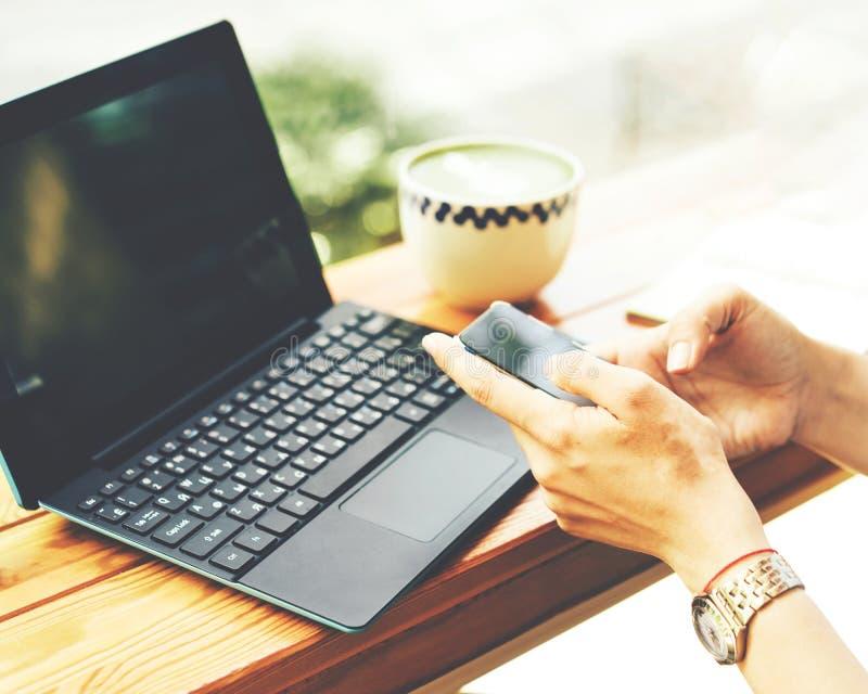 膝上型计算机和电话在手上在咖啡馆 库存图片