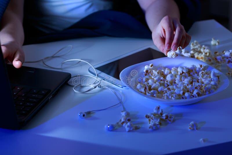 膝上型计算机和碗玉米花 免版税库存图片