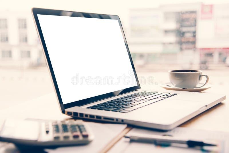 膝上型计算机在有笔和咖啡计算器的一张书桌被安置 免版税库存图片