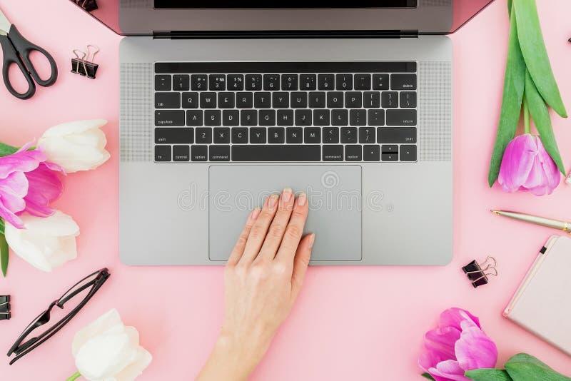 膝上型计算机妇女工作 妇女工作区用女性手、膝上型计算机、郁金香、辅助部件和日志在桃红色背景 顶视图 Fl 免版税库存图片