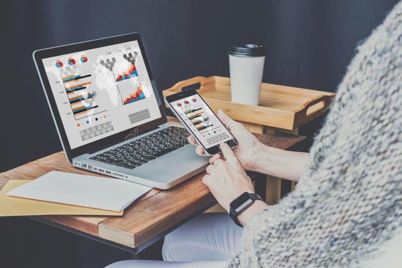 膝上型计算机特写镜头在木桌和智能手机上的有图表、图和图的在屏幕上在女实业家的手上 库存照片