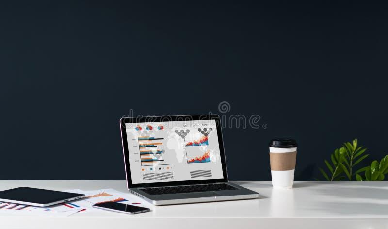 膝上型计算机特写镜头有图表、图和图的在白色桌上的屏幕上 免版税图库摄影