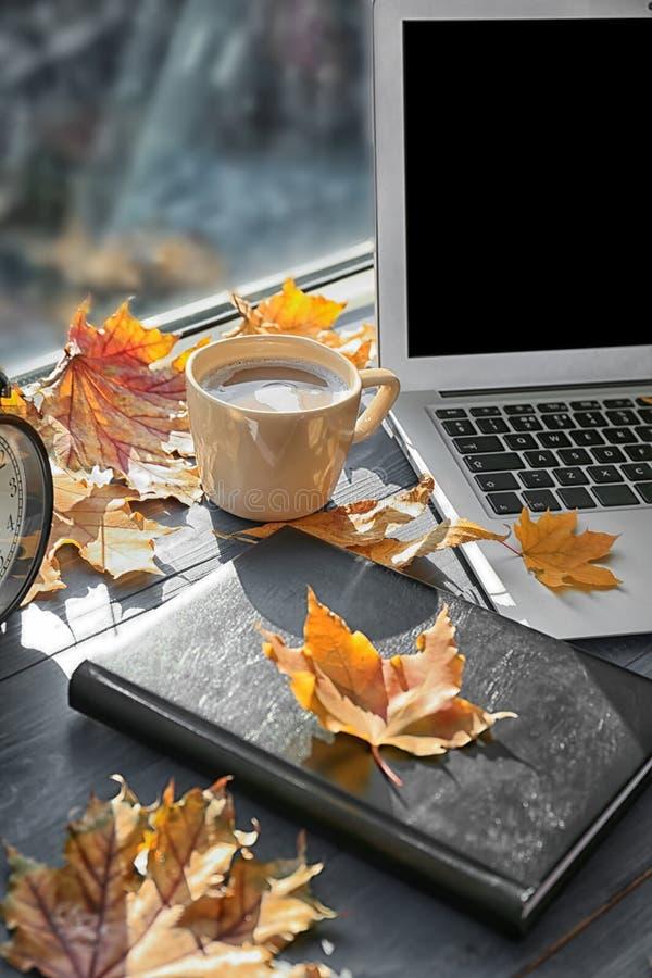 膝上型计算机用咖啡、书和秋叶在窗台 库存照片