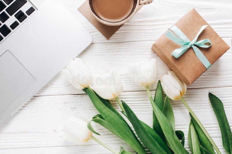 膝上型计算机用早晨咖啡和郁金香和时髦的礼物盒在wh 库存图片