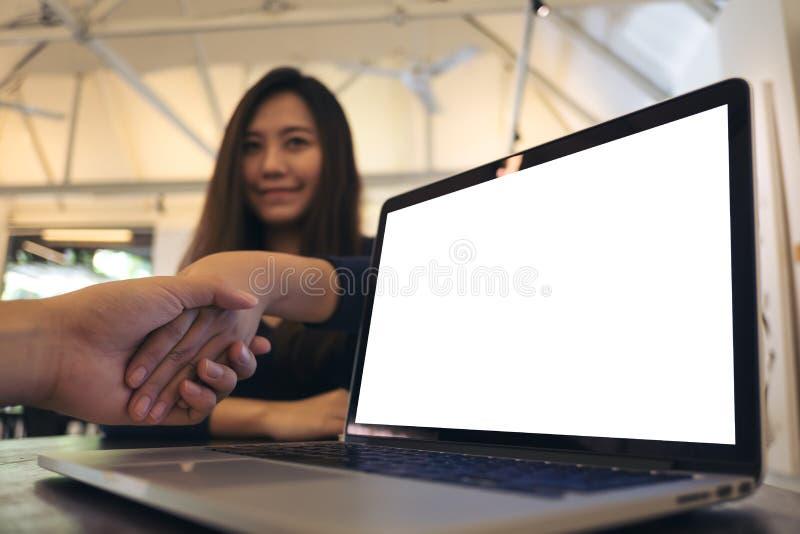 膝上型计算机的大模型图象有空白的白色屏幕的在与商人的木震动的桌和女实业家上手 库存照片