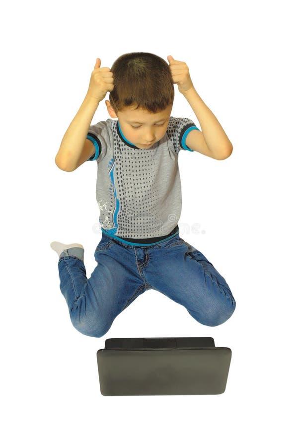 从膝上型计算机的男孩困窘 库存照片