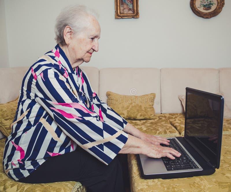 膝上型计算机高级键入的妇女 免版税库存照片