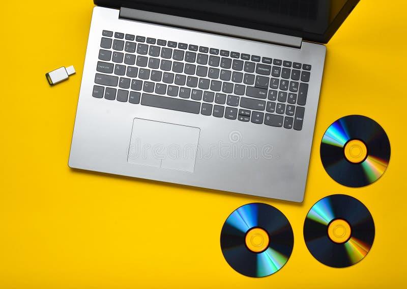膝上型计算机,光盘驱动器, USB在黄色背景的闪光驱动 现代和过时的数字式媒介 库存图片