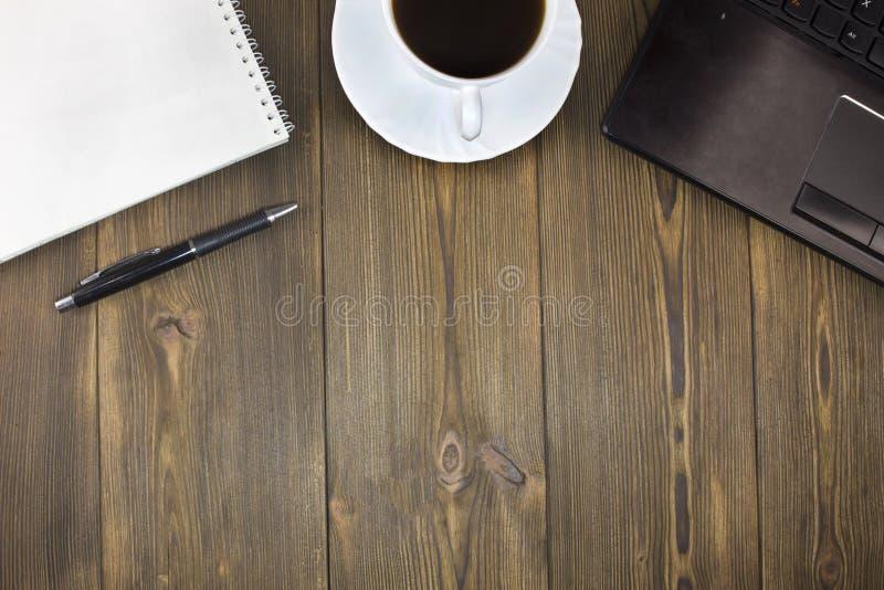 膝上型计算机,咖啡,在一个木桌笔记本的笔记薄笔 免版税库存照片