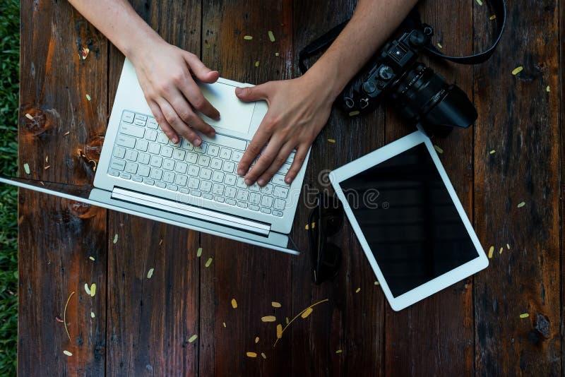 膝上型计算机,在木背景的照相机 自由职业者或单独企业家工作地点平的位置  免版税库存照片
