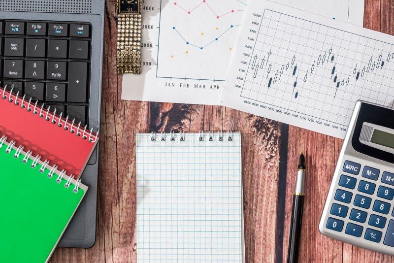 膝上型计算机,股票市场数据,与计算器和笔 库存图片