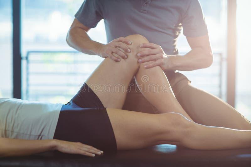 给膝盖疗法的生理治疗师妇女 图库摄影