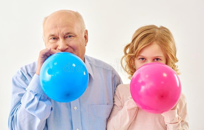 膨胀气球的孙女和祖父在演播室 免版税库存照片