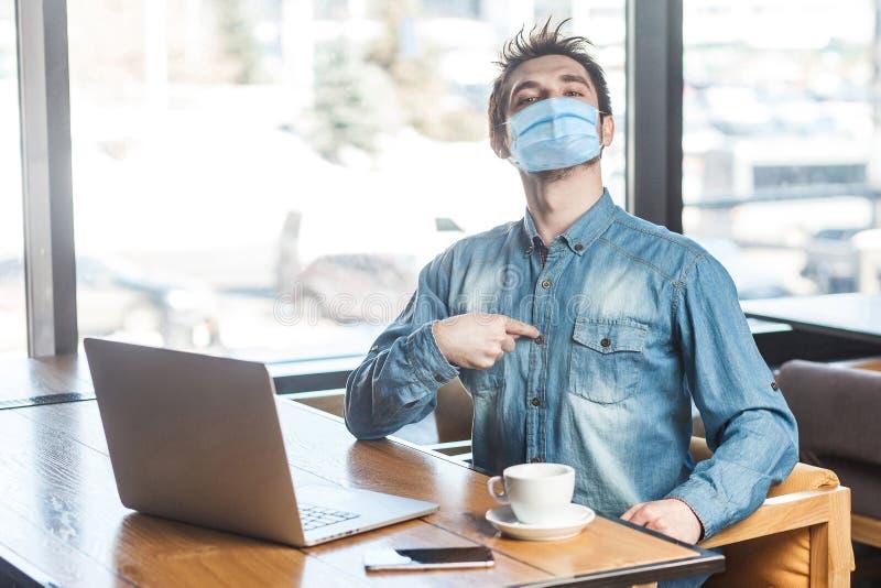 自信满满、自负的年轻男子的肖像,他戴着蓝色衬衫的外科医用口罩,坐着,在笔记本电脑上工作, 库存照片