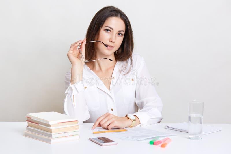 自信的企业家在企业文献工作,在嘴附近保留eyewear,为业务会议做准备 美丽的螺柱 免版税库存图片