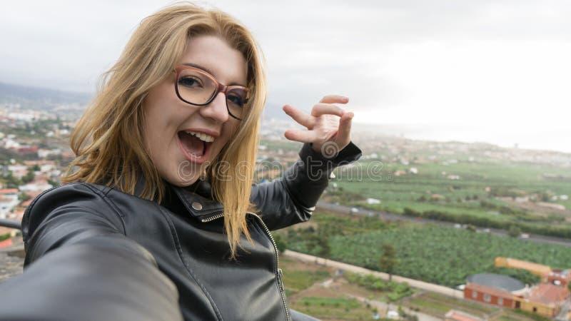 自信的金发女性用相机拍照 戴短发微笑牙齿眼镜的青少年 图库摄影