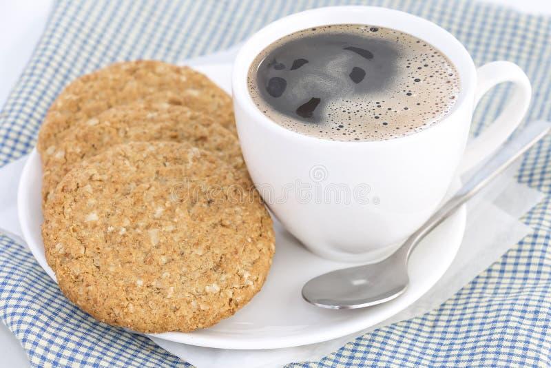 自创一种油脂含量较高的酥饼由燕麦粥制成堆积与在布料和纸的热的咖啡杯在白色桌背景 概念 免版税库存图片