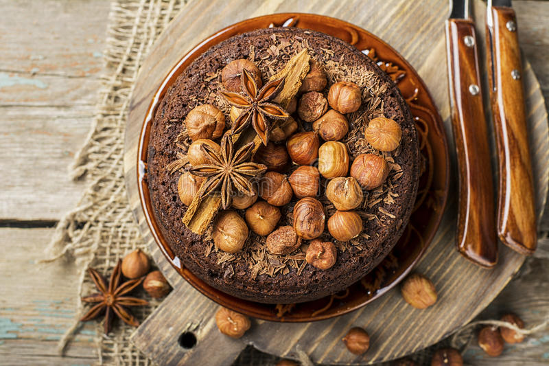 自创与巧克力片、胡说的榛子、桂香和香料的巧克力疯狂的蛋糕一个舒适秋天茶会的 顶层 免版税库存照片
