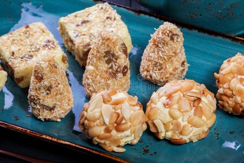 自创乳脂状的乳脂软糖糖果用椰子,葡萄干,坚果,芝麻 库存图片
