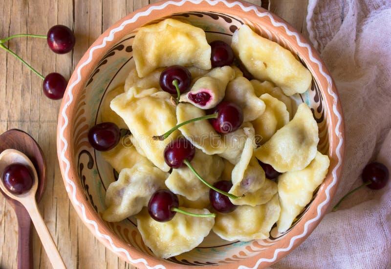 自创传统俄国乌克兰饺子vareniki用在陶器的樱桃 免版税库存照片
