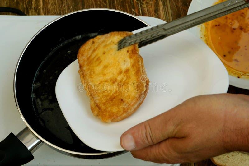 自创厨房 白面包油煎方型小面包片或多士,浸泡在一个被搅拌的鸡鸡蛋,在油煎的煎锅油煎在小 免版税库存照片
