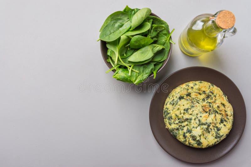 自创可口土豆蛋菜肉馅煎蛋饼用在板材的菠菜 在瓶的食谱成份橄榄油在灰色厨房用桌上 免版税库存图片